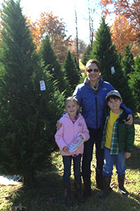 A happy family poses in the orchard of cut-your-own fresh Christmas Trees at New Castle Farms in Forrest City, Arkansas.